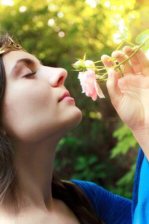 beautiful medieval princess sniffing pink wild rose Stock Photo - 8562368