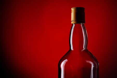 bottle of whiskey on deep red background photo