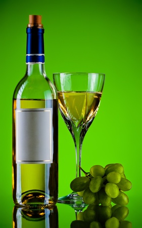bottle and glass of wine, grape bunch, green background photo