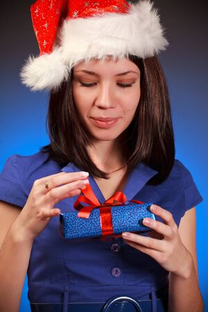 beautiful christmas girl opening gift, blue background photo