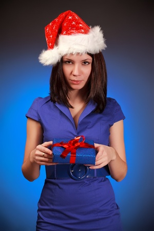 beautiful christmas girl with gift, blue background photo