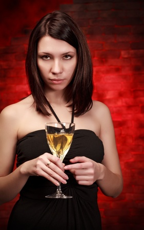 beautiful girl with glass of wine, red background photo