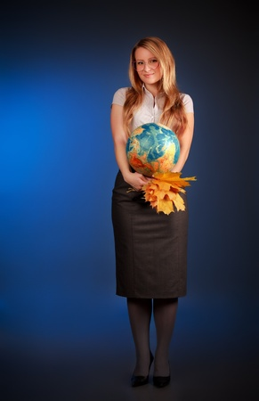 pretty teacher with globe and maple leaves, blue background photo
