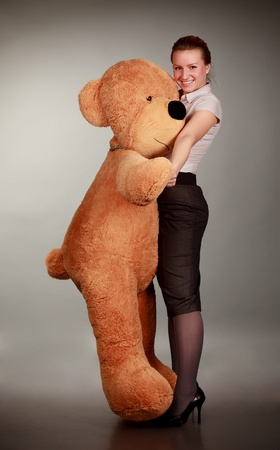 beautiful girl dancing with funny toy bear photo