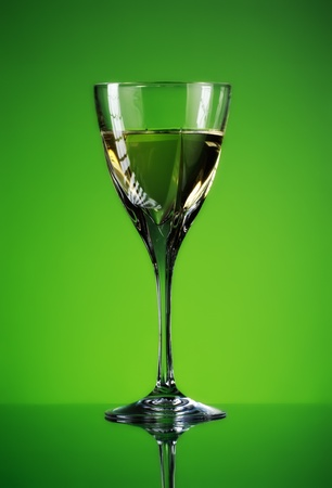 glass of white wine on green background photo