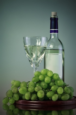 bottle and glass of wine, grape bunch, gray background photo