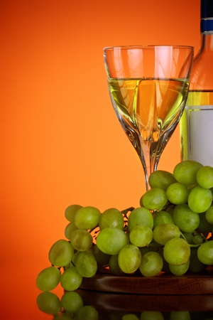 glass of wine and grape bunch, red background photo