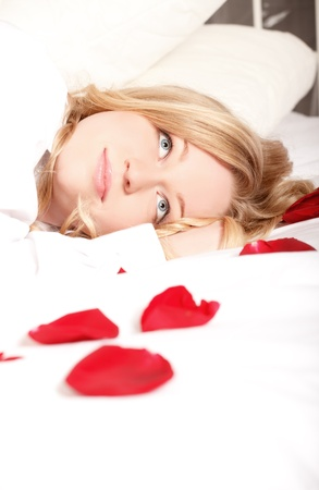blonde woman in bed with red rose petals photo