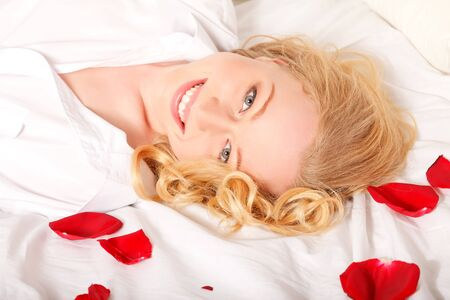 happy blonde woman in bed with red rose petals Stock Photo - 8787138