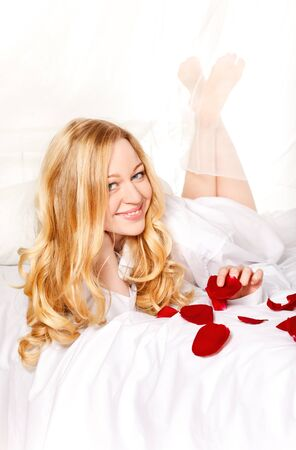 happy blonde woman in bed with red rose petals photo