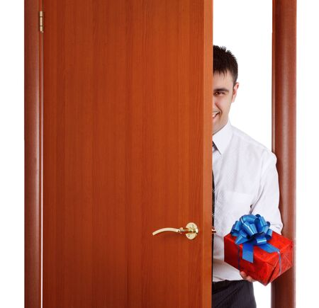 young man with gift opening the door photo