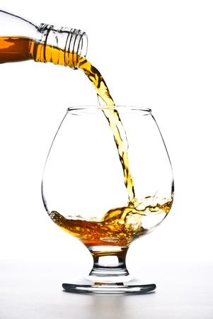 botella de licor: co�ac verter en el vidrio sobre fondo blanco