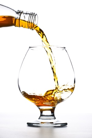 cognac pour into the glass over white background photo