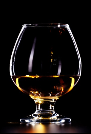 elegant whiskey glass isolated on black background photo