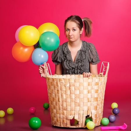 funny girl with basket of toys and balloons, red background photo