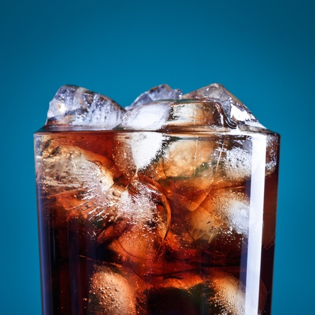 drinking soda: glass of cola with ice on blue background