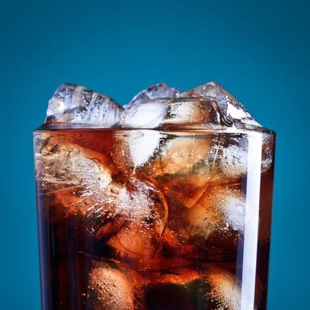 gaseosas: vidrio de cola con hielo sobre fondo azul Foto de archivo