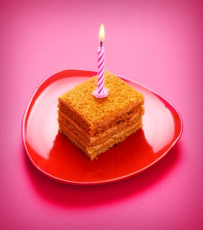 birthday cake with candle on pink background photo