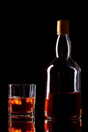 botella de whisky: botella y vaso de whisky en fondo negro Foto de archivo