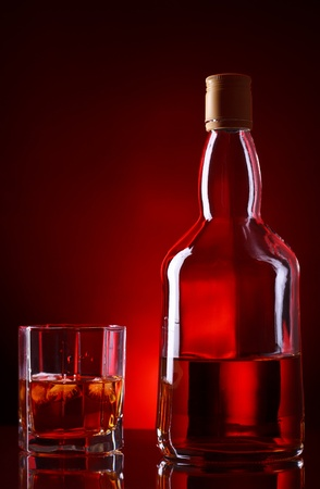 aperitive: whiskey bottle and glass on red background