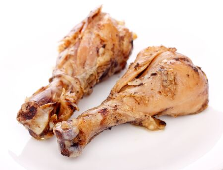 two crispy fried chicken legs on a white dish photo