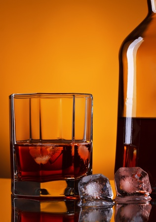 whiskey bottle and glass on yellow background photo