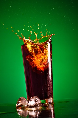 glass with splashing cola on green background photo