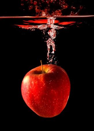 Apple cayendo al agua con splash sobre fondo negro