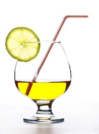 cocktail in glass with slice of lime and straw photo