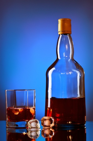 whiskey bottle and glass on blue background photo