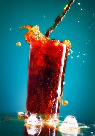 pouring cola in glass over blue background photo