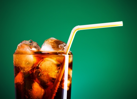 fizzy: glass of cola with ice and straw on green background