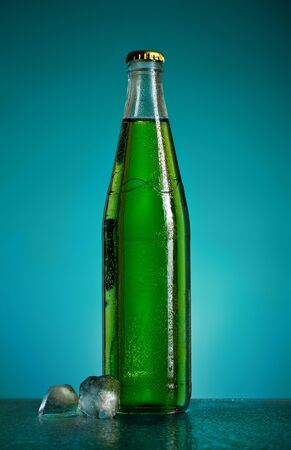 green soda bottle and ice cubes, blue background photo