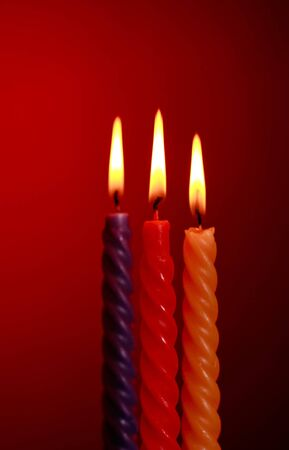 three twisted burning candles over red background photo