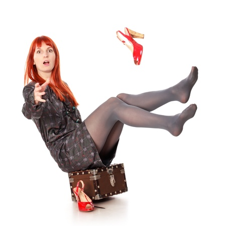 extravagant woman falling from her suitcase and screams, isolated on white