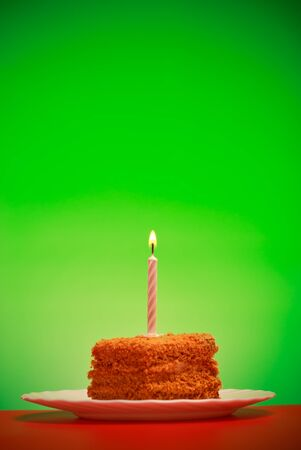 one item: birthday cake with candle on pink background Stock Photo