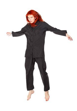 levitacion: mujer asombrada en kimono negro volando, aislado en blanco