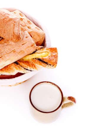 basket with buns and mug of milk on white Stock Photo - 9183830