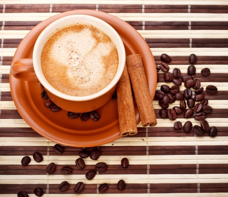 fresh coffee cup and beans on bamboo napkin photo