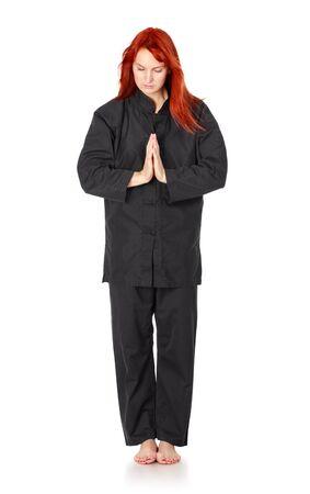 aikido: girl in black kimono regards, isolated on white