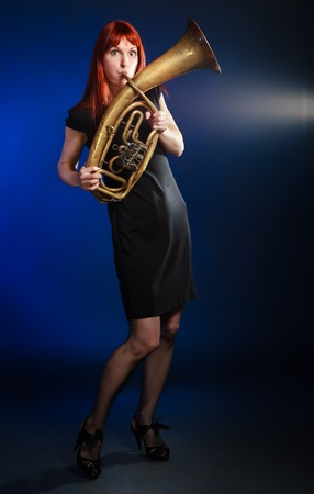 girl in black dress with trumpet, blue background Stock Photo - 9246133