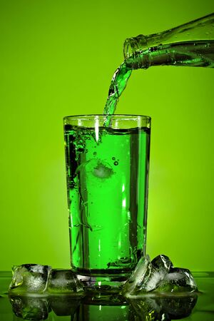 pouring soda in glass over green background photo