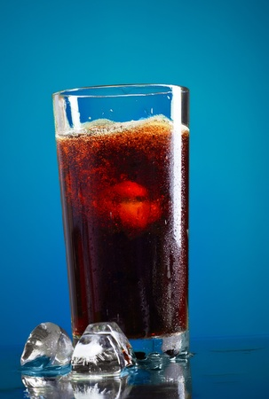 the carbonation: glass of cola with ice on blue background