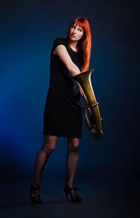 girl in black dress with trumpet, blue background Stock Photo - 9477777