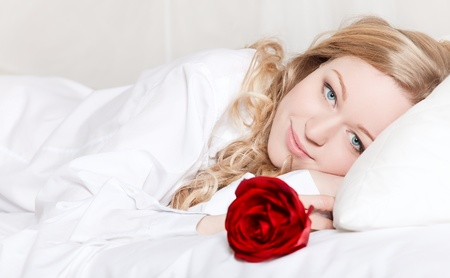 portrait of pretty woman laying in bed with red rose photo