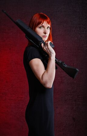 woman in black dress with sniper rifle, red background photo