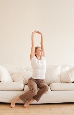 cute young girl relaxing and stretches on couch at home photo