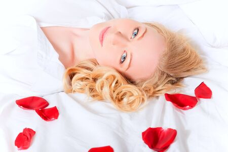 portrait of pretty woman laying in bed with rose petals photo