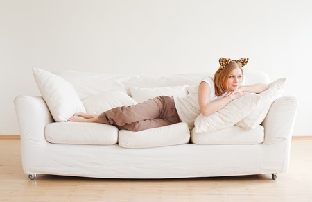 cute young woman with neko ears dreaming on couch photo