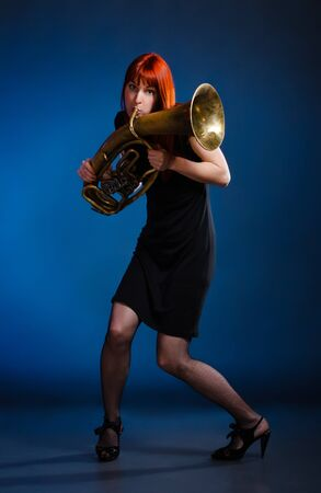 girl in black dress with trumpet, blue background Stock Photo - 9654436